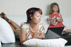 Een jonge moeder met een notitieboekje en een dochter Royalty-vrije Stock Fotografie