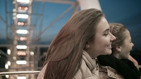 Een jonge moeder met haar dochter op het Reuzenrad bij schemer is gelukkig met het leven! stock video