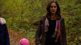 Een jonge moeder met haar twee kinderengangen door het de herfstbos dat zij langs de bosweg hebben gelopen Zij zijn gelukkig stock footage