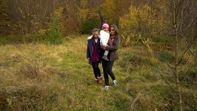 Een jonge moeder met haar twee kinderengangen door het de herfstbos dat zij langs de bosweg hebben gelopen Zij zijn gelukkig stock videobeelden
