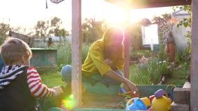 Een jonge moeder met een kind die in de zandbak spelen De zomerdag, zonstralen op de Speelplaats stock footage