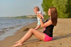 Een jonge moeder met een kleine dochter zit op een zandig strand stock fotografie