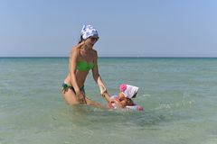 Een jonge moeder met een kleine dochter zwemt in het overzees stock foto