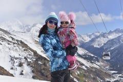 Een jonge moeder reist in de bergen met haar weinig dochter op de Zonnige winter stock afbeelding