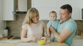 Een jonge moeder treft voorbereidingen om haar 10 maand oude zoon te eten De vader bevindt zich naast hem en houdt het kind in zi stock video
