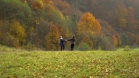 Een jonge moederspelen met haar weinig dochter in de van de de herfst bosmamma en dochter roes die rond merrily, handen houden stock footage