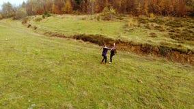 Een jonge moederspelen met haar weinig dochter in de van de de herfst bosmamma en dochter roes die rond merrily, handen houden stock videobeelden