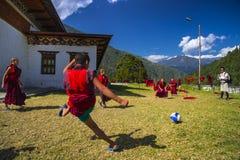 Een jonge monnik schoot een doel, de voetbal van het monnikenspel Trashiyangtse Dzong, oostelijke Bhutan stock afbeeldingen