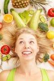 Een jonge mooie die vrouw door groenten en vruchten wordt omringd royalty-vrije stock fotografie