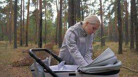 Een jonge mooie moeder gaat met een wandelwagen in het Park en communiceert met de baby stock videobeelden
