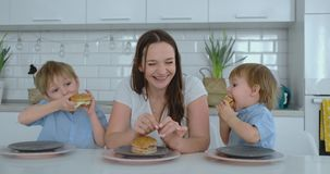 Een jonge mooie moeder in een witte kleding met twee kinderen glimlacht en eet verse burgers in haar keuken gelukkig stock videobeelden
