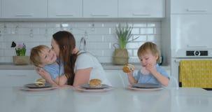 Een jonge mooie moeder in een witte kleding met twee kinderen glimlacht en eet verse burgers in haar keuken gelukkig stock video