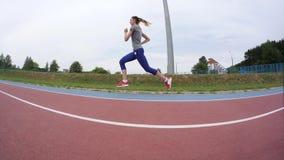 Een jonge mooie vrouw die jogger voorbij de camera tijdens een dag lopende opleiding lopen bij het stadsstadion in langzame motie stock videobeelden