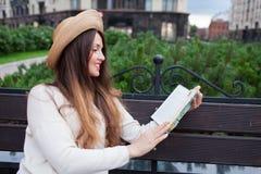 Een jonge mooie vrouw in een elegante hoed zit op een bank in een nieuwe woonbuurt en leest een document boek Zij knipt thro weg royalty-vrije stock afbeeldingen