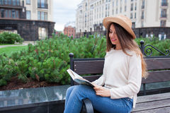 Een jonge mooie vrouw in een elegante hoed zit op een bank in een nieuwe woonbuurt en leest een document boek Zij knipt thro weg stock foto