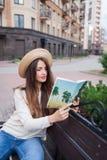 Een jonge mooie vrouw in een elegante hoed zit op een bank in een nieuwe woonbuurt en leest een document boek Zij knipt thro weg royalty-vrije stock foto