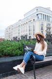 Een jonge mooie vrouw in een elegante hoed zit op een bank in een nieuwe woonbuurt en leest een document boek Zij knipt thro weg stock afbeeldingen