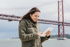 Een jonge mooie vrouw gebruikt een tablet om met vrienden te communiceren of bekijkt een kaart of iets anders Brug 25 April Stock Foto's