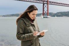 Een jonge mooie vrouw gebruikt een tablet om met vrienden te communiceren of bekijkt een kaart of iets anders Brug 25 April Stock Afbeeldingen