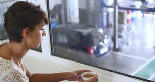 Een jonge, mooie vrouw het drinken koffie bij de Bandmontage stock video