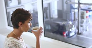 Een jonge, mooie vrouw het drinken koffie bij de Bandmontage stock videobeelden
