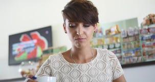 Een jonge, mooie vrouw het drinken koffie bij de Bandmontage stock footage