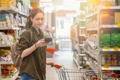 Een jonge mooie vrouw rolt een kruidenierswinkelkar en leest informatie over het geselecteerde product Bewust consumptieconcept stock foto