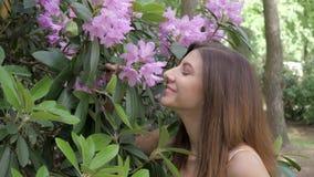 Een Jonge Mooie Vrouwen Ruikende Tot bloei komende Purpere Bloemen stock footage
