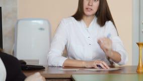 Een jonge mooie zwangere vrouw in een zwarte T-shirt spreekt binnen aan een jonge vrouwelijke arts in een witte laag in haar bure stock video