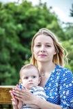 Een jonge mum met een kleine babyzoon openlucht op een bank bij de zomer royalty-vrije stock foto