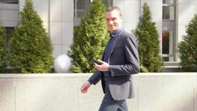 Een jonge onderaan de straat lopen en zakenman die terwijl het onderzoeken van de camera glimlachen stock video