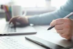 Een jonge ontwerper houdt een pen van een tablet in van hem stock foto