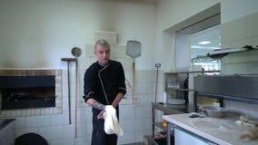 Een jonge pizzamaker bereidt pizza in de keuken van het restaurant voor De kok roteert het deeg in de lucht en spreidt uit stock footage