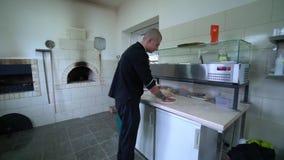 Een jonge pizzamaker bereidt pizza in de keuken van het restaurant voor De kok roteert het deeg in de lucht Langzame Motie stock videobeelden