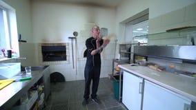 Een jonge pizzamaker bereidt pizza in de keuken van het restaurant voor De kok roteert het deeg in de lucht Langzame Motie stock footage