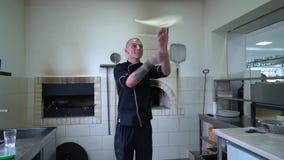 Een jonge pizzamaker bereidt pizza in de keuken van het restaurant voor De kok roteert het deeg in de lucht Langzame Motie stock video