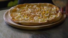 Een jonge pizzamaker bereidt pizza in de keuken van het restaurant voor De kok snijdt de pizza in stukken met een mes stock videobeelden