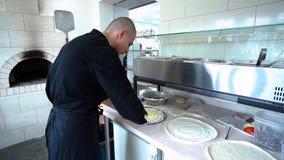 Een jonge pizzamaker bereidt pizza in de keuken van het restaurant voor De kok spreidt de witte saus over het deeg uit en stock footage