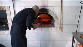 Een jonge pizzamaker bereidt pizza in de keuken van het restaurant voor De kok zet pizza in een hete oven en draait over het stock videobeelden