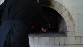 Een jonge pizzamaker bereidt pizza in de keuken van het restaurant voor De kok zet pizza in een hete oven en draait over het stock footage