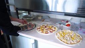 Een jonge pizzamaker bereidt pizza in de keuken van het restaurant voor Bereidt zwarte pizza voor De kok giet geraspt stock videobeelden