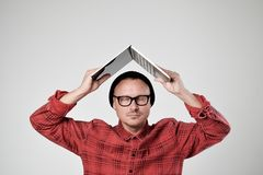 Een jonge programmeur in een zwarte hoed houdt laptop in zijn han stock afbeelding