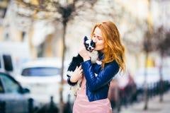 Een jonge redhaired Kaukasische vrouw met sproeten houdt en kust, omhelzend zwart-witte ruwharige hond van Chihuahua-ras meisjesd stock foto