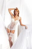 Een jonge redhead vrouw in witte erotische lingerie Royalty-vrije Stock Afbeeldingen