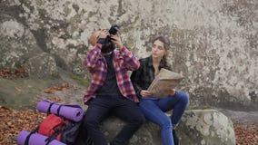 Een jonge reisfotograaf met een camera, turistkaart en een rugzakzitting met een jong meisje op een rots en het bekijken bij stock videobeelden