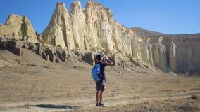 Een jonge reiziger drinkt water tegen de rotsen Stock Foto