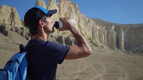 Een jonge reiziger drinkt water tegen de rotsen Royalty-vrije Stock Afbeelding