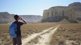 Een jonge reiziger drinkt water tegen de rotsen Stock Foto's