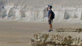 Een jonge reiziger drinkt water tegen de rotsen Royalty-vrije Stock Fotografie