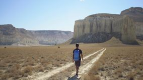 Een jonge reiziger loopt langs een weg op een bergachtig gebied Stock Afbeeldingen